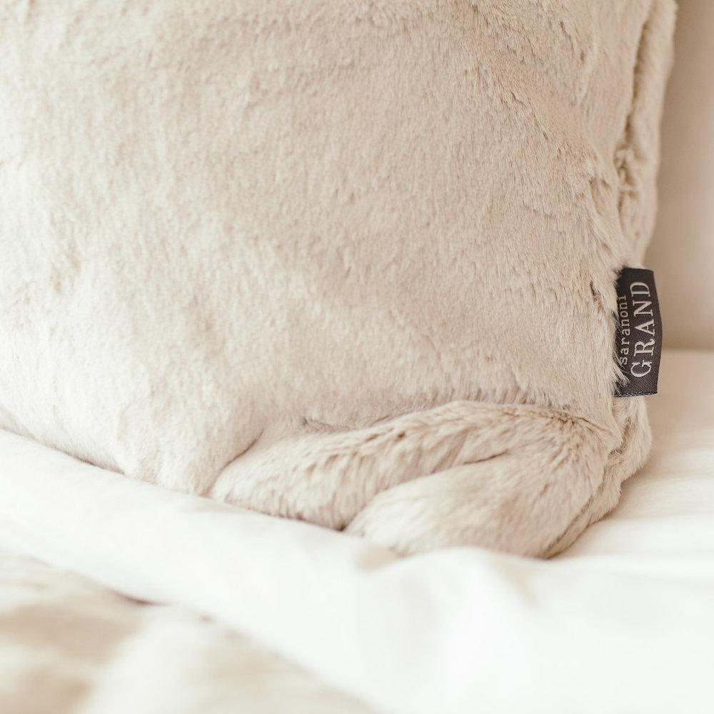 Corner of luxurious light tan faux fur euro pillow.