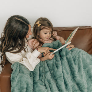 Sisters read a book together under a cozy earthy green throw blnaket.