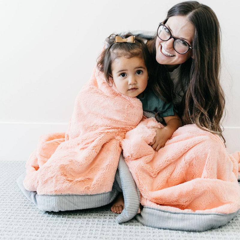 Mom and toddler daughter snuggled up in an warm melon lush blanket.