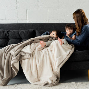 Mother cuddling with young children under an oversized ivory and gray throw blanket.