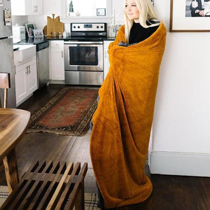 Cute girl enjoying her morning wrapped up in a sandstone large throw blanket.