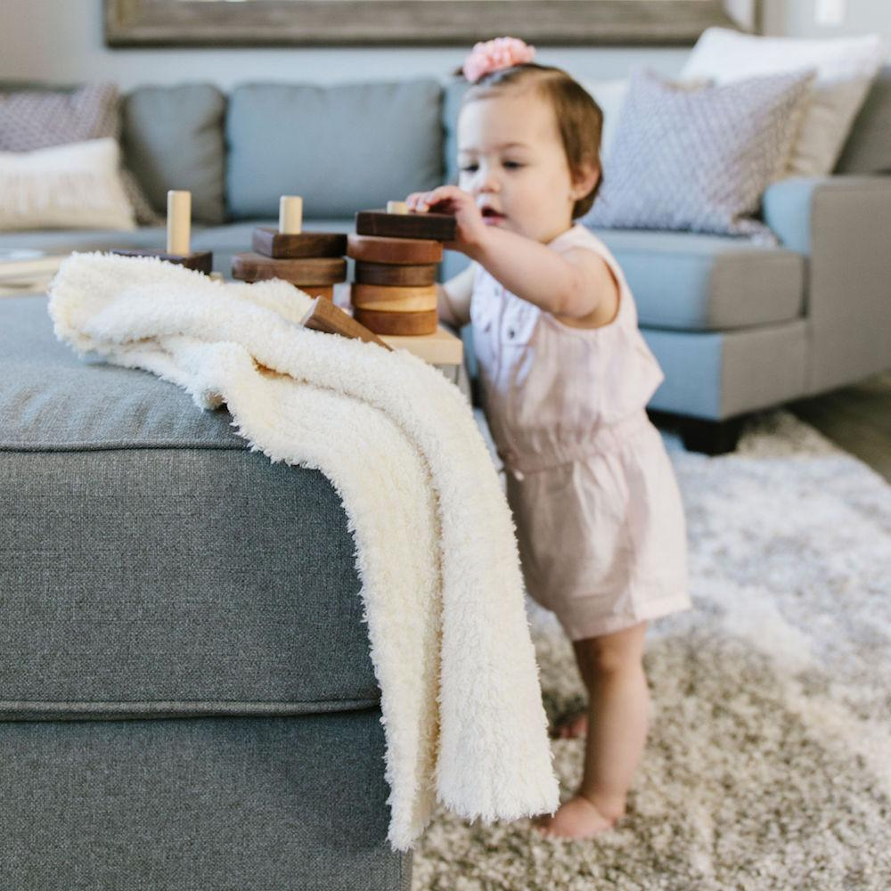 Cute toddler plays with her toys next to a light weight ivory baby blanket.