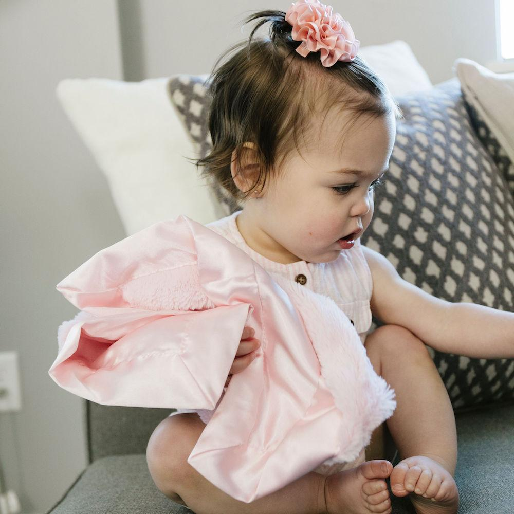 Baby girl clutches her Saranoni mini blanket with a pink plush front and a silky, satin back.