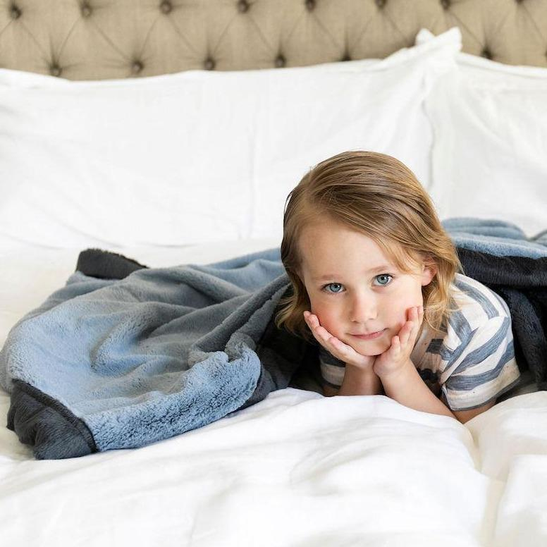 Little girl poses on the bed under her dusty blue full size lush blanket.