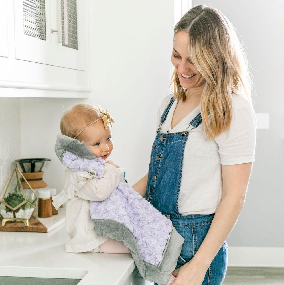 Baby girl sits on the counter with mom clutching a lavender plush lovey blanket.