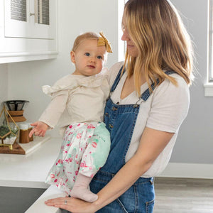 Mom and baby hang out in the kitchen with her floral print baby lovey.
