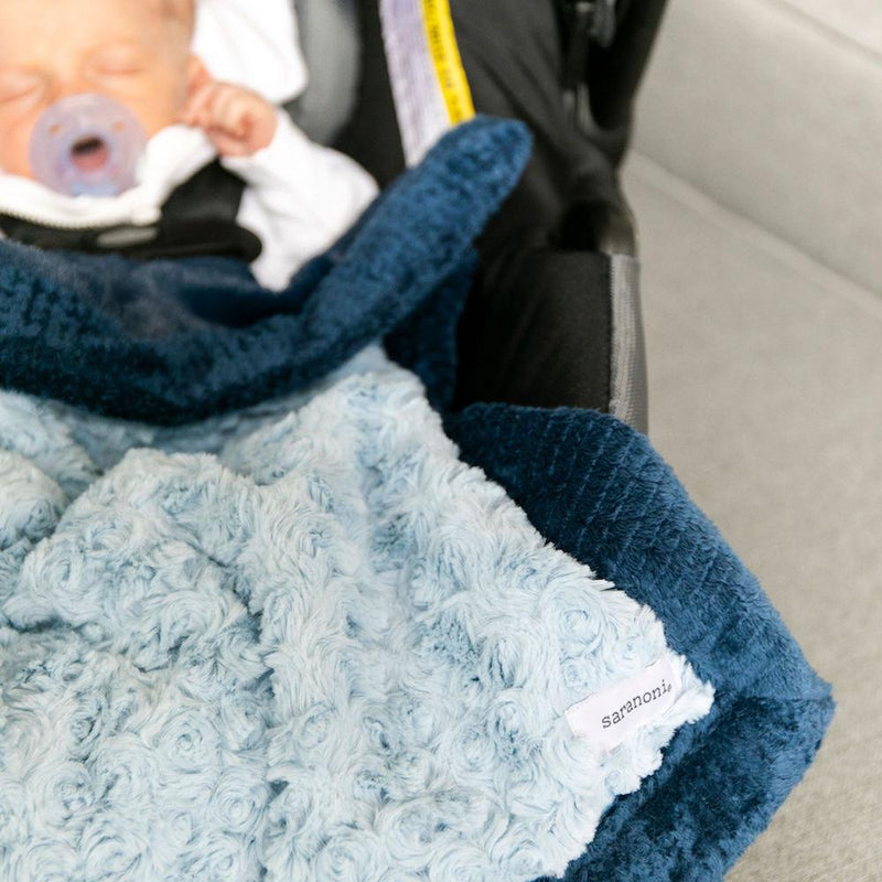 Baby boy sleeping with his blue two-toned car seat blanket.