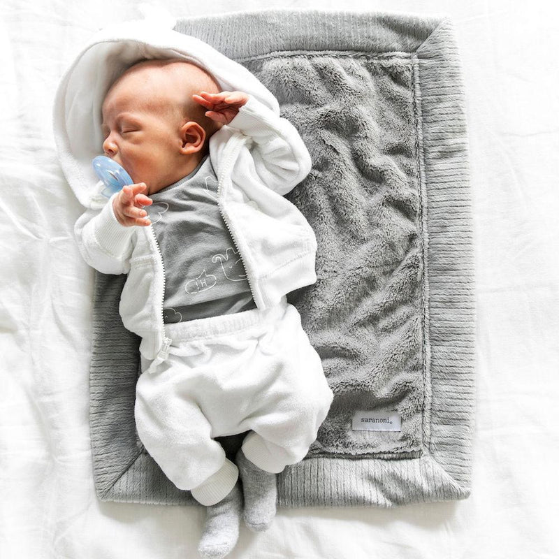 Baby boy sleeping on plush, neutral mini baby bedding.