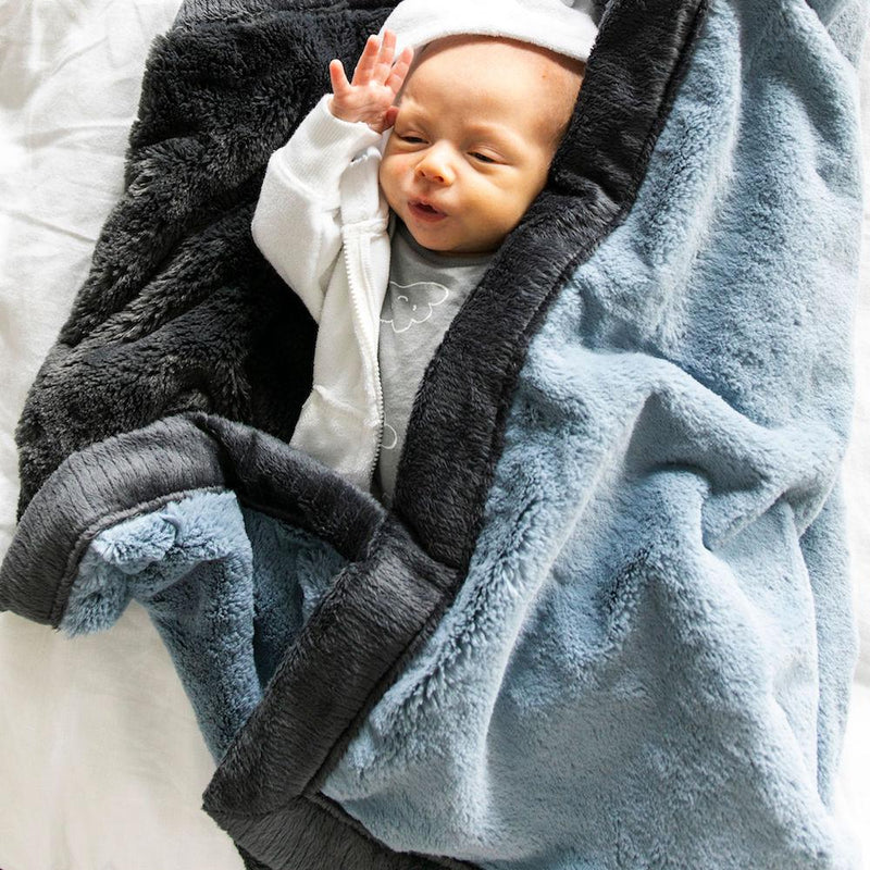 Newborn baby boy wrapped in gray blue blanket with charcoal trim