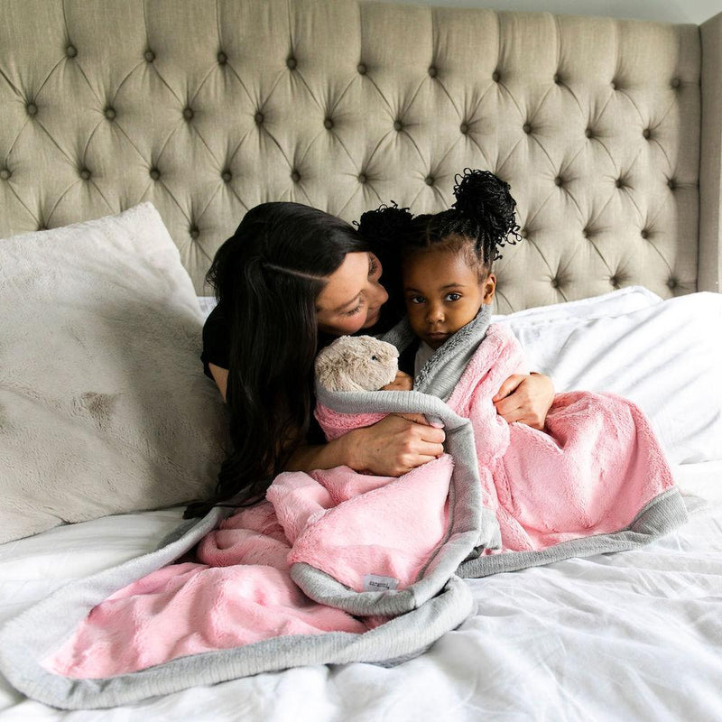 Mom and daughter cuddle on the bed wrapped in a gorgeous pink and gray lush girls throw blanket.