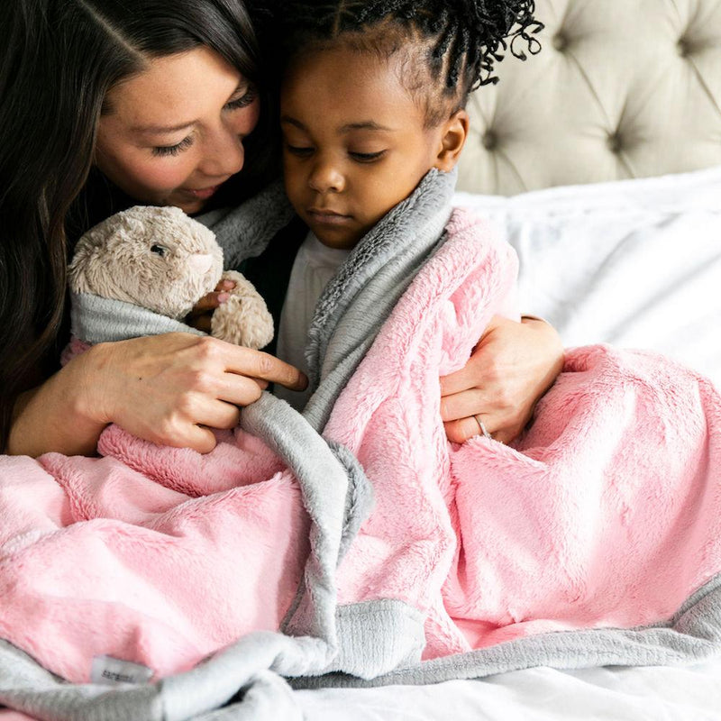 Little girl being comforted by her mom while holding her stuffed bunny and being wrapped in her light pink blanket.