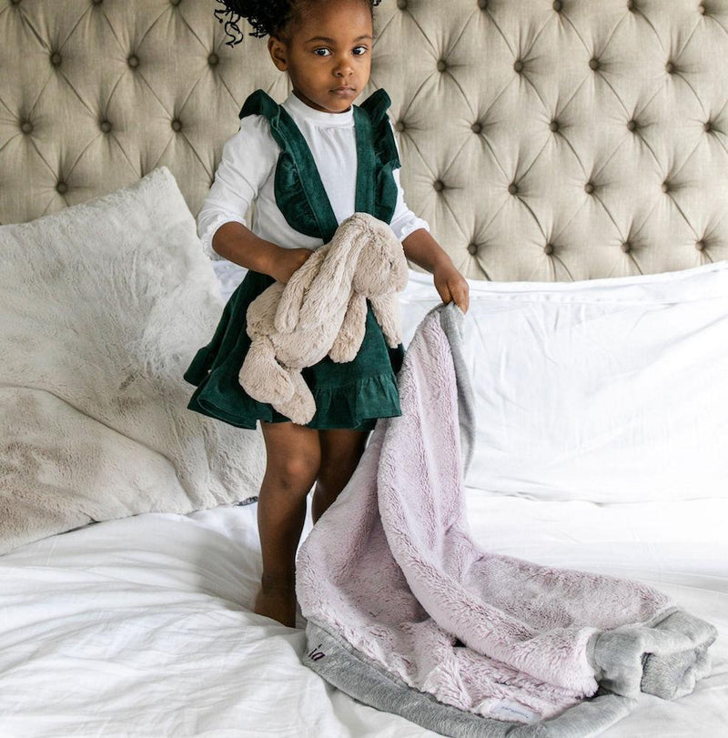 Little girl standing on the bed clutching her plush, lilac kids blanket.