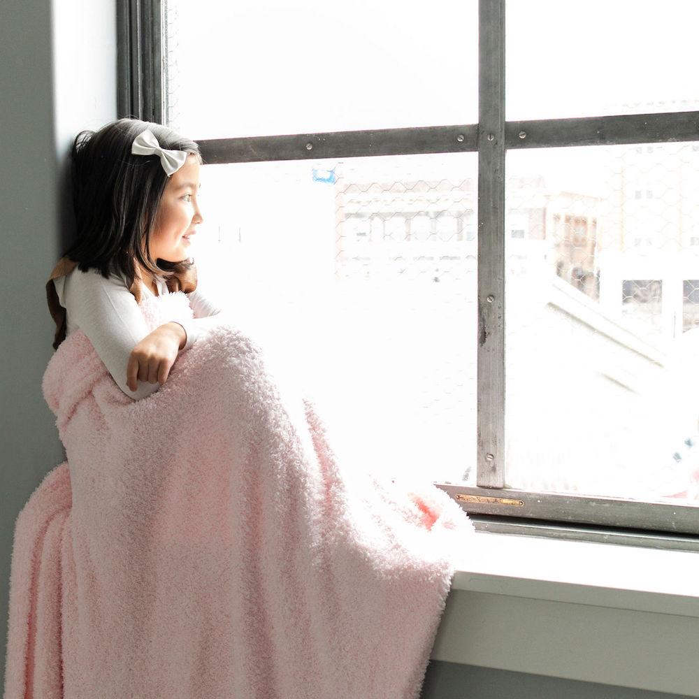 Little girl sits in the window wrapped in light pink stretchy kids blanket.