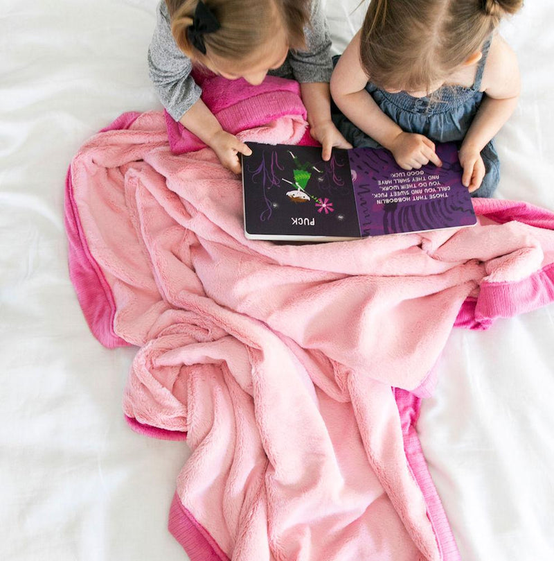 Girls read books together with their pink two-toned blanket throw draped over their legs.