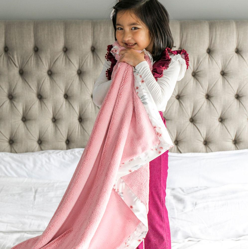 Young girl hugs her soft pink blanket with floral satin.