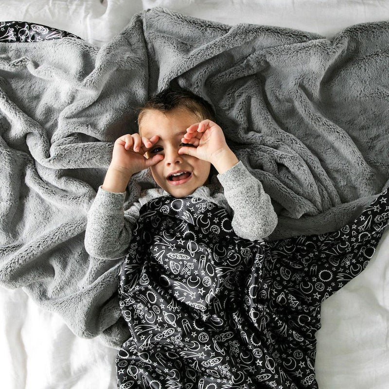 Boy playing under a gray plush blanket with black Launch Day satin back.