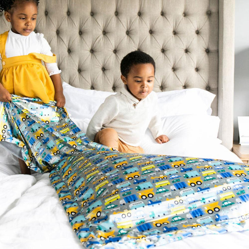 Kids play on the bed with oversized lush and satin blanket patterned with cars and trucks.