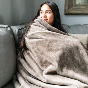 Girl snuggles with a super soft fuax fur adult throw.