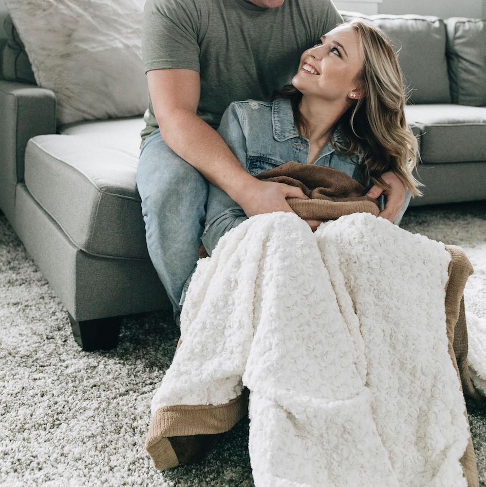 Wife lovingly gazes up at husband as he covers her in a cozy and luxurious extra large ivory swirl throw blanket.