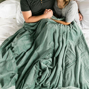Husband and wife holding hands while wrapped up in a beautiful eucalyptus green, large winter blanket.