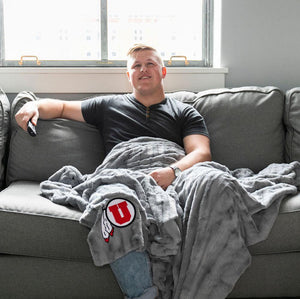 College student watches T.V. with a large gray plush University of Utah blanket draped across his legs.