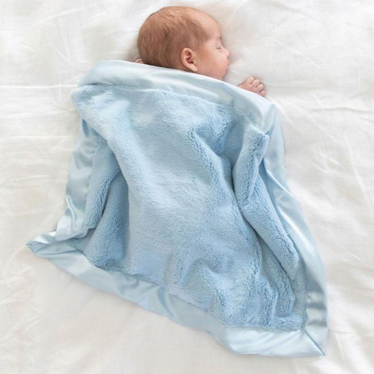 Newborn boy sleeps on a bed with a beautiful light blue plush and satin baby blanket spread over him.