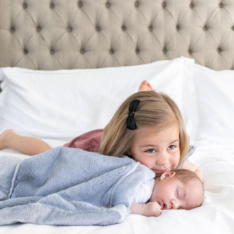 Cute sister giving her baby brother some love, while baby boy is snuggled in a warm blue blanket for babies.