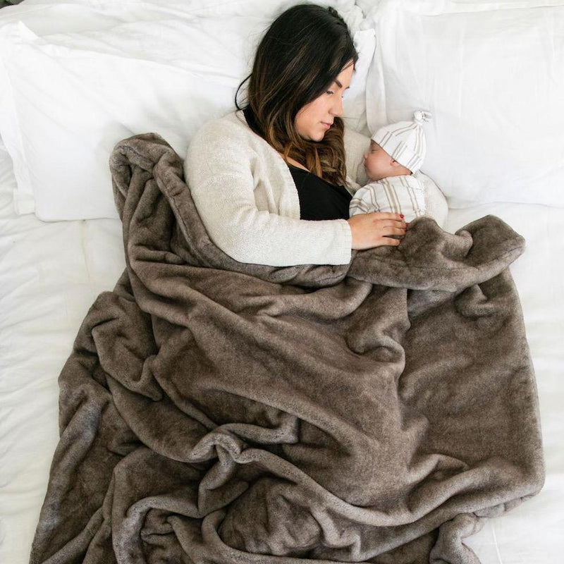 Mom cuddles newborn under animal fur throw blnaket.