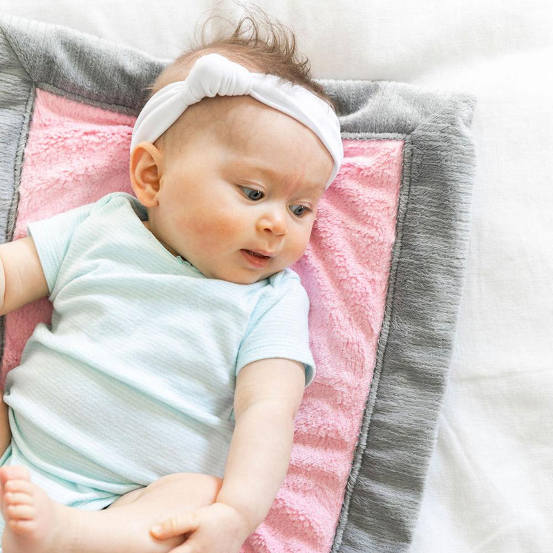 Newborn girl laying on a pink and gray Saranoni mini, the best baby blanket.