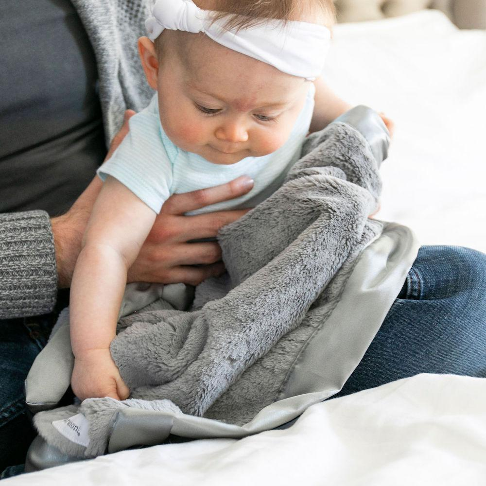 Baby plays on mother's lap with a velvety soft gray baby blanket.