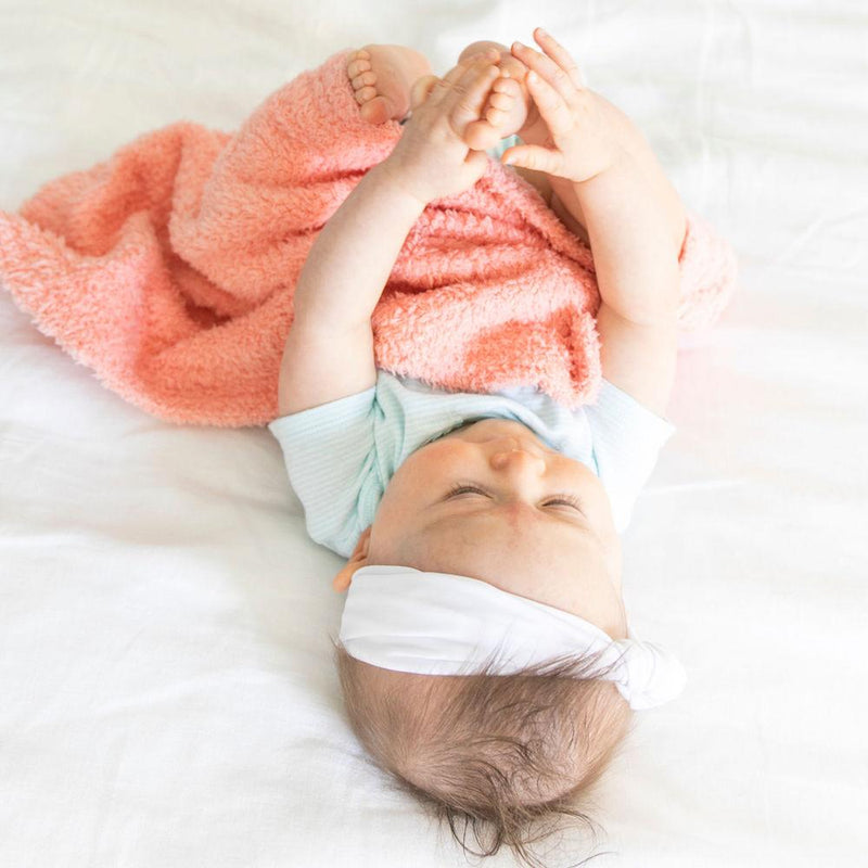 Baby girl plays under a fluffy and breathable peach lovey for babies.