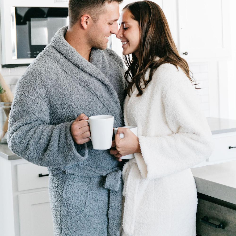 Couple share a cup of coffee together while in coordinating gray and ivory robes.