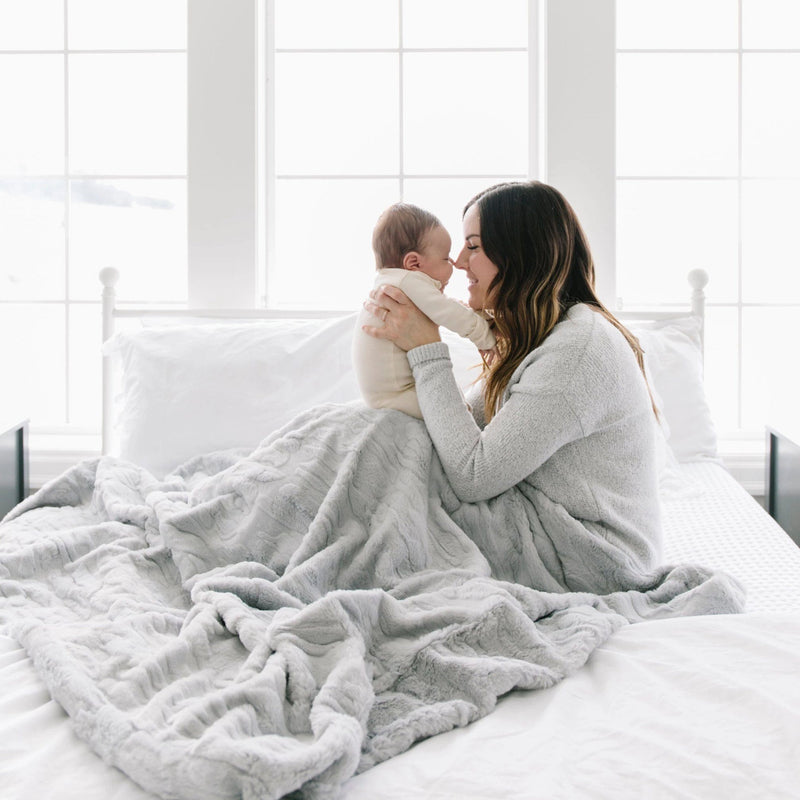 Mom sits with her newborn on her bed while sitting under a silver gray weighted blanket