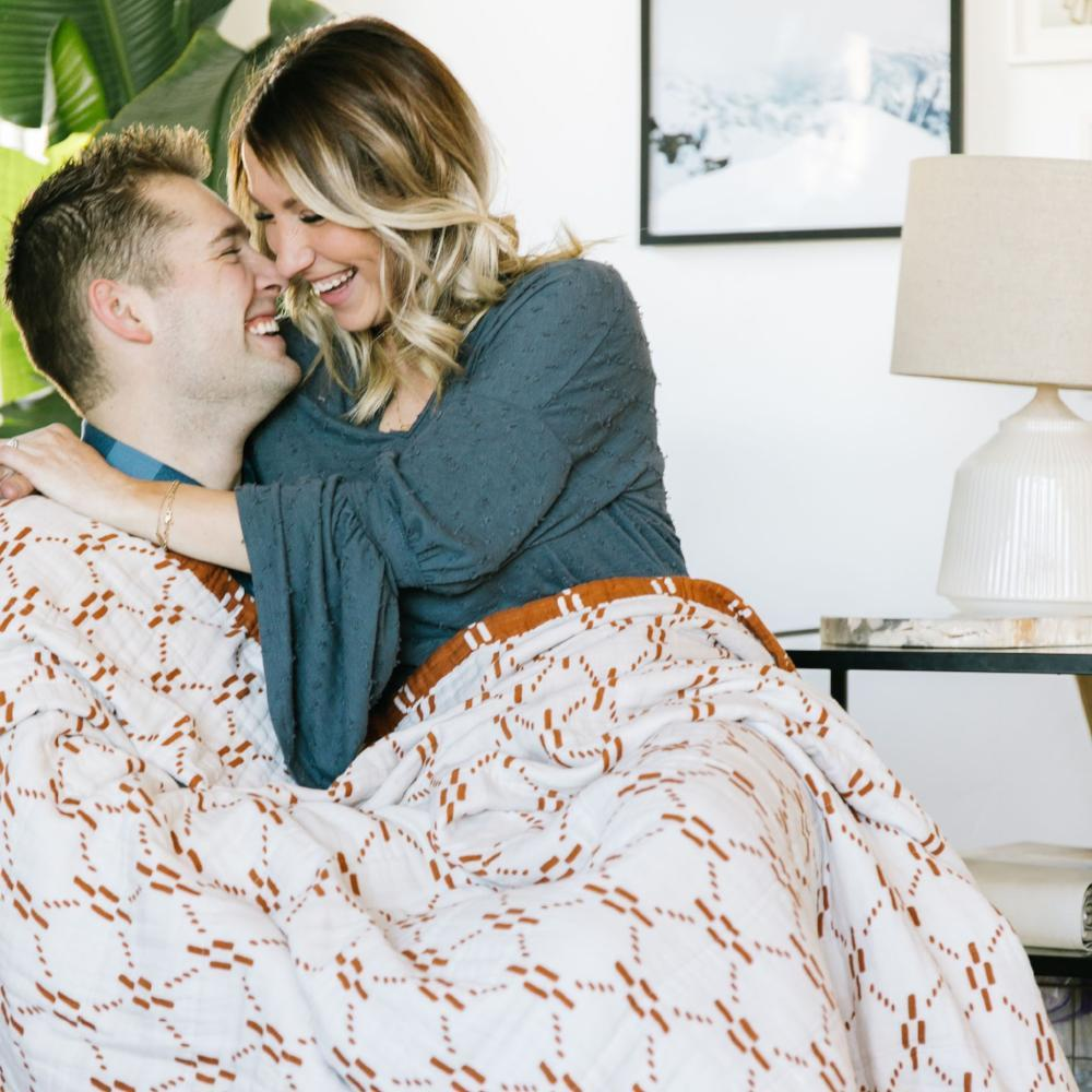 Husband and wife embracing wrapped in a white and copper muslin blanket.