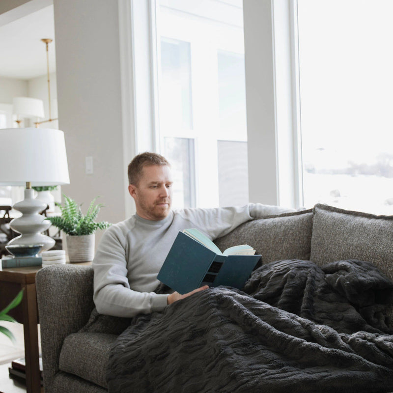 Man sits under charcoal weighted blanket while sitting on the couch and reading a book
