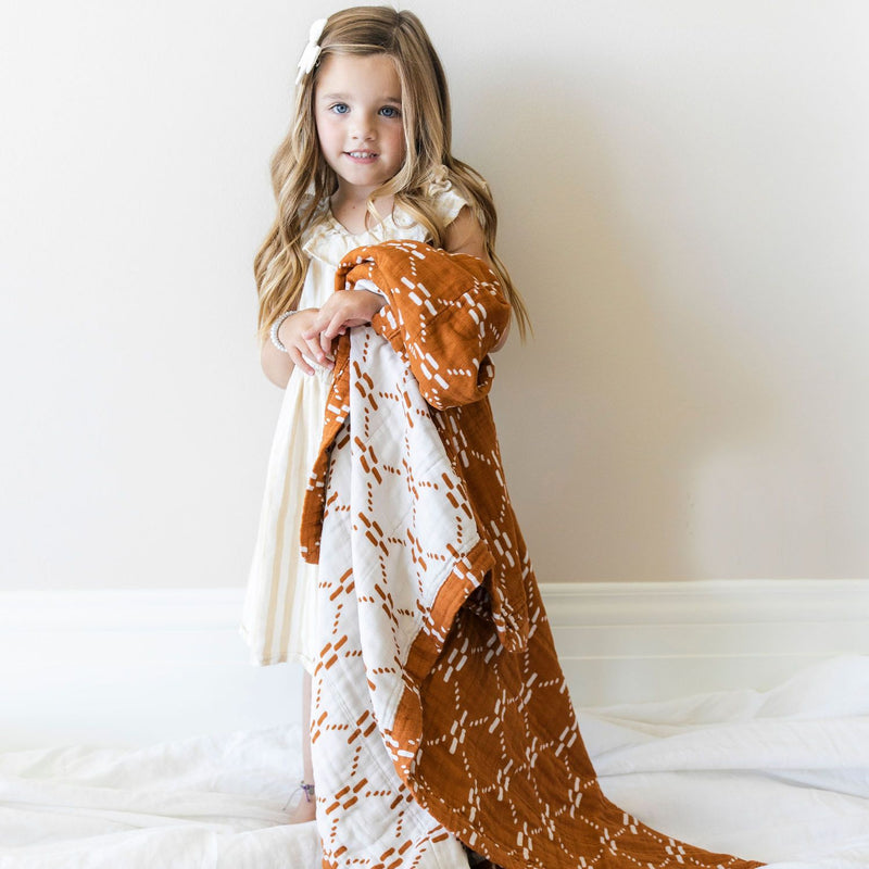 Little girl with blonde curly hair holds lightweight rust and white quilt.