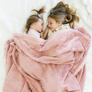 Sisters lay on bed under dusty pink kids blanket