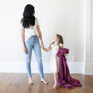 Little girl stands hand in hand with her mom while holding a pretty purple kids blanket.