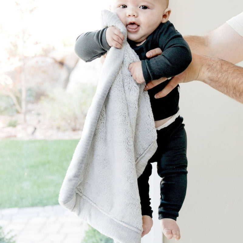 Little boy snuggling gray lovey blanket