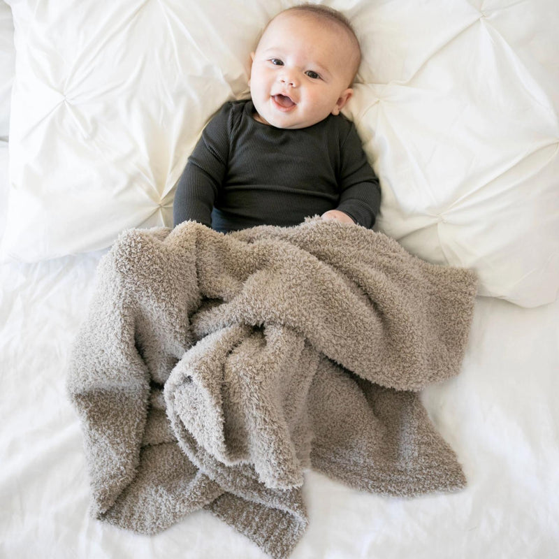 Baby smiling with his tan stretchy blanket.
