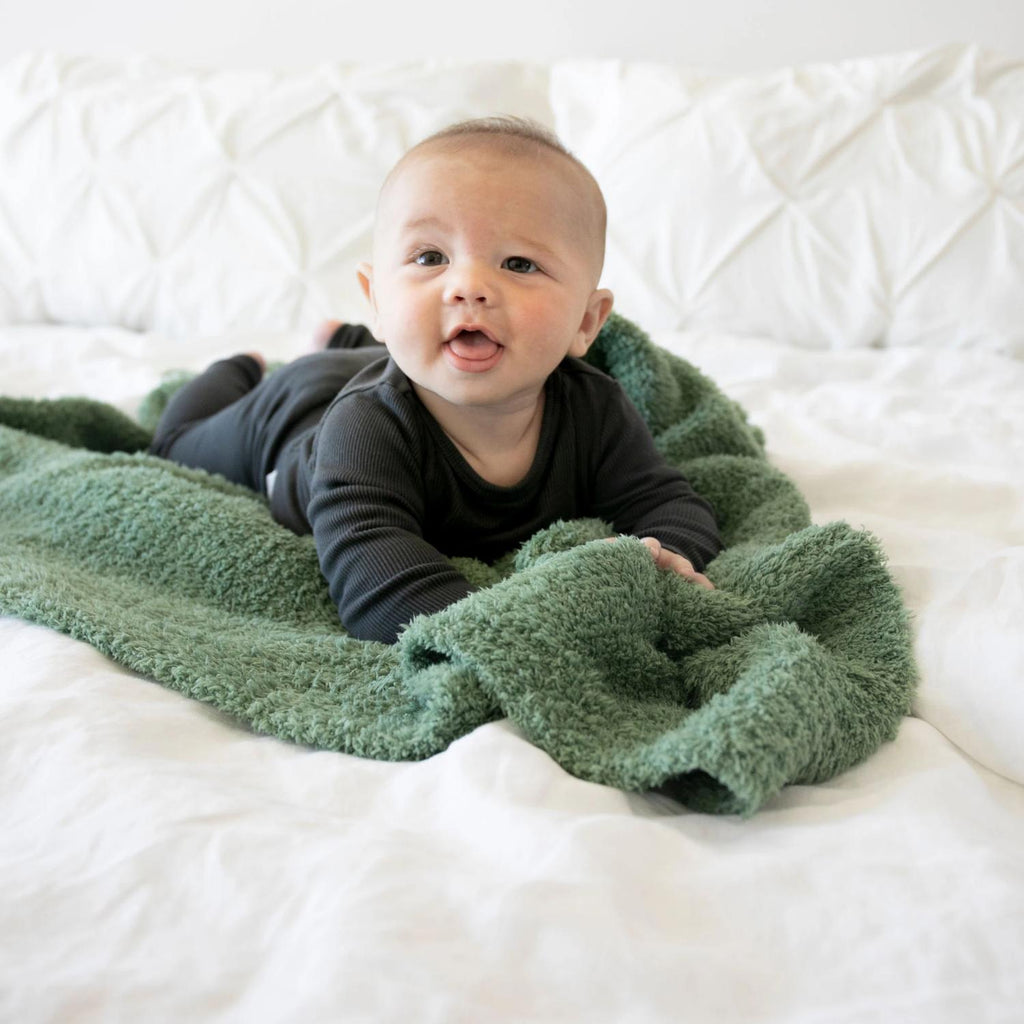 Little boy lays on tummy on top of beautiful grass green blanket