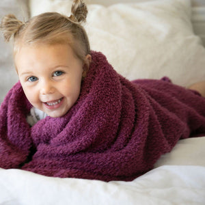 Little girl wrapped in cozy purple blanket.