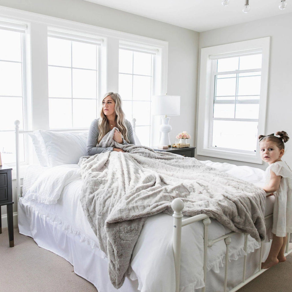Mom sits on the bed under warm gray blanket while daughter climbs on the end of the bed.