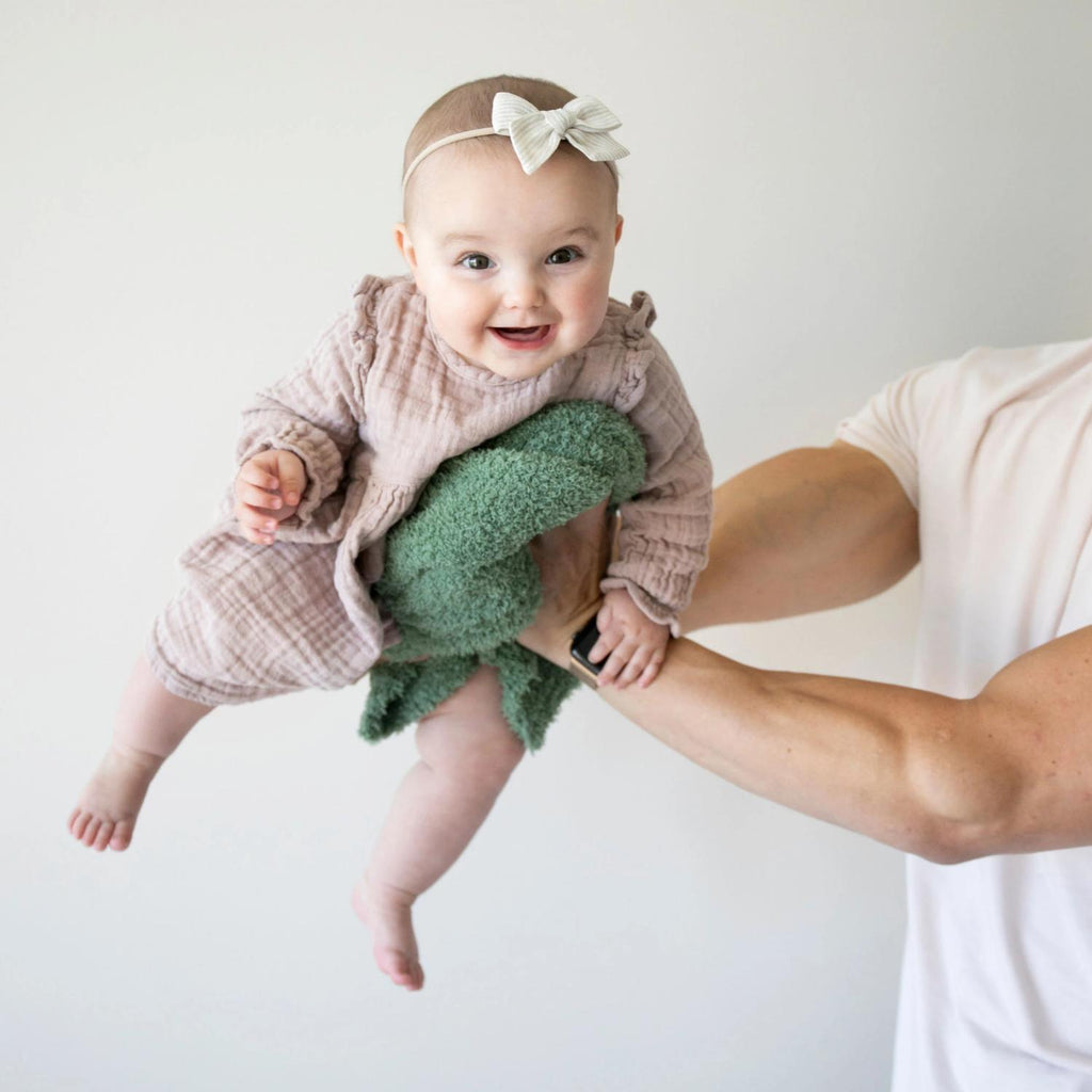 Dad holds baby girl up while holding an olive green lovey.