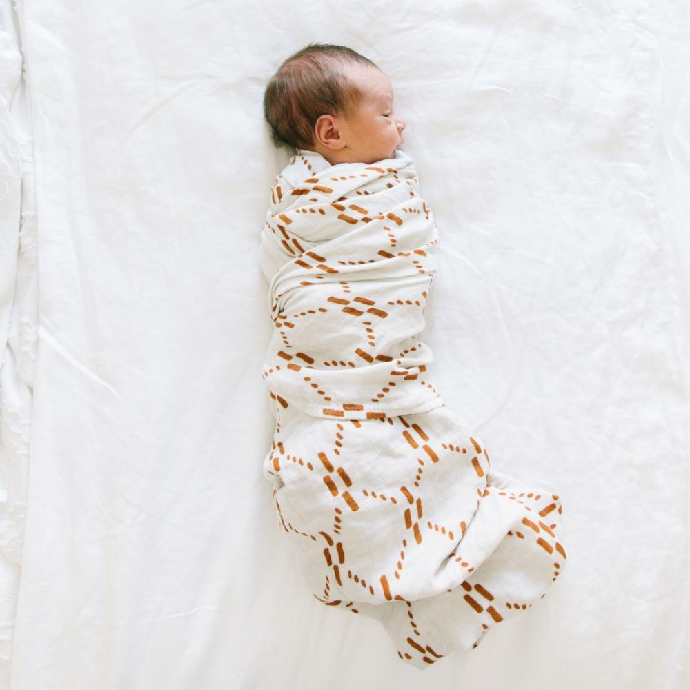 Baby swaddled in white and copper newborn wrap.