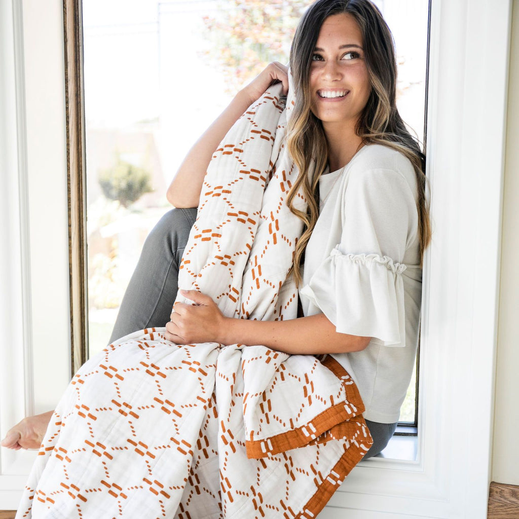 Woman sits in the window with white and orange patterned blanket on her lap.