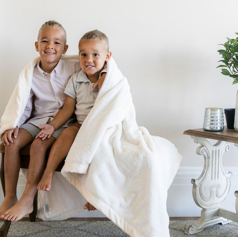 Two brothers sitting on a bench wrapped in a white full sized blanket