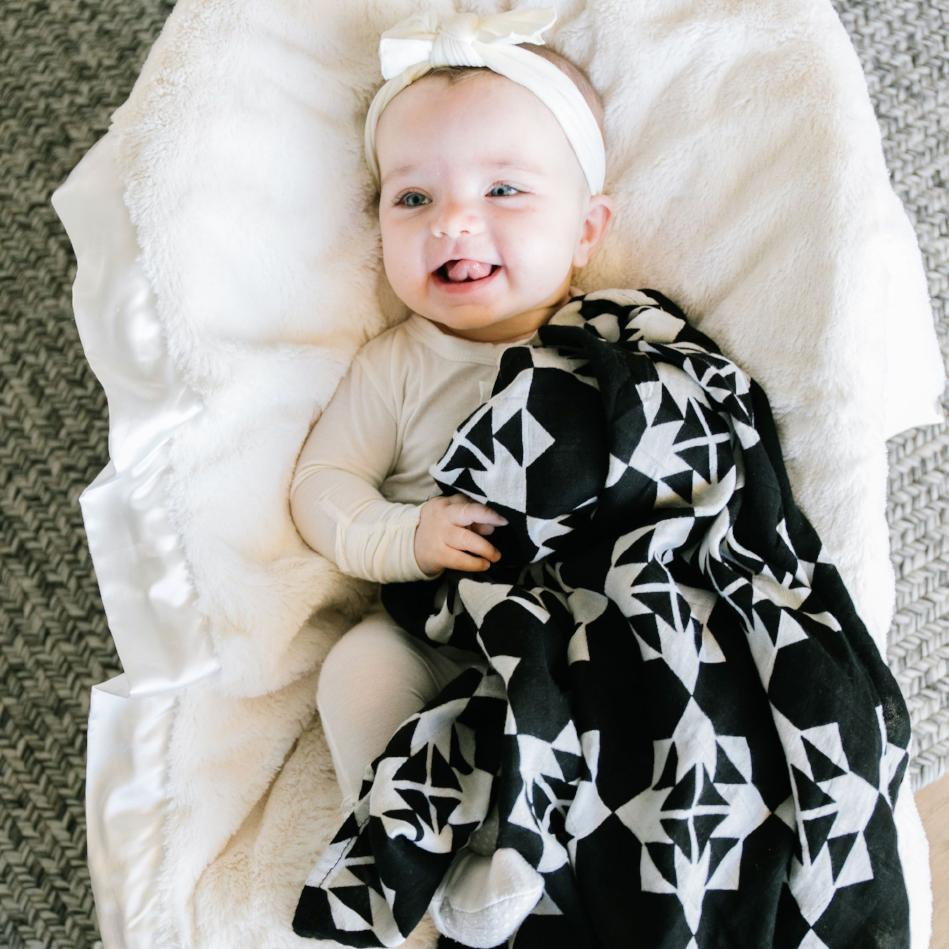 Baby girl laying in a basinet playing with her black and white muslin baby blanket.