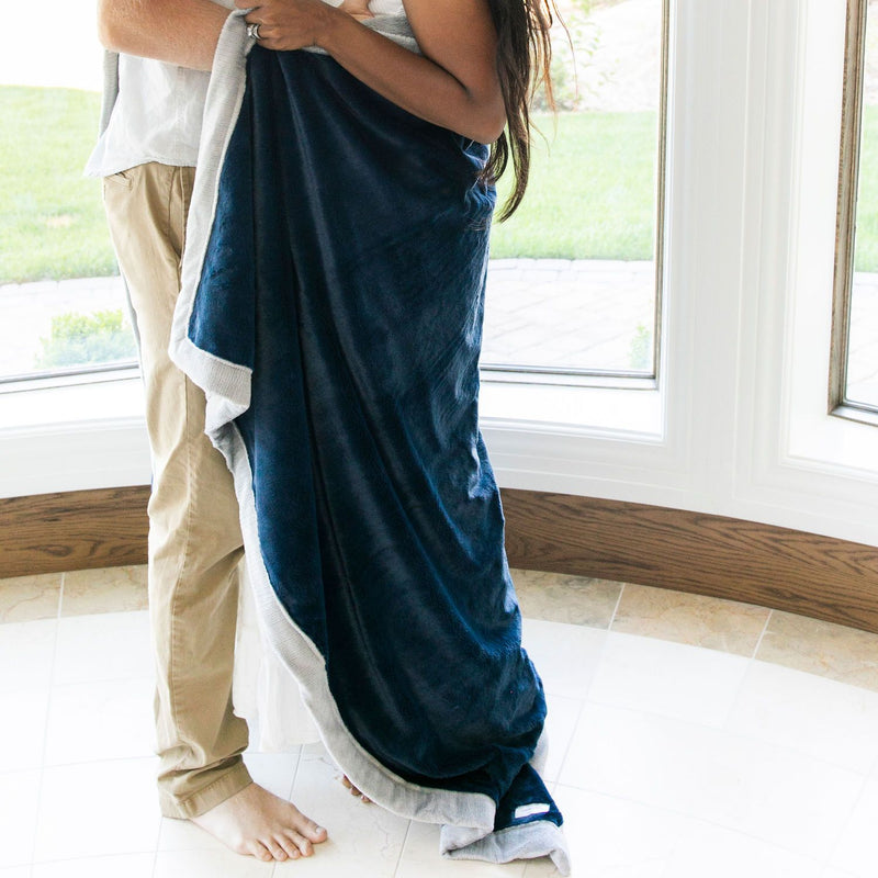 Couple wrapped in dark navy fuzzy oversized blanket
