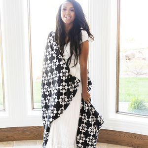 Woman wrapped in black and white extra large muslin blanket.